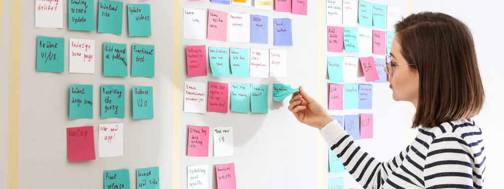 Woman removing sticky note from a wall as part of the scrum process