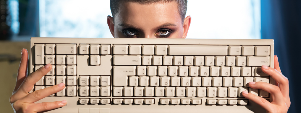 Young woman with short hair holding a retro keyboard over her nose and mouth