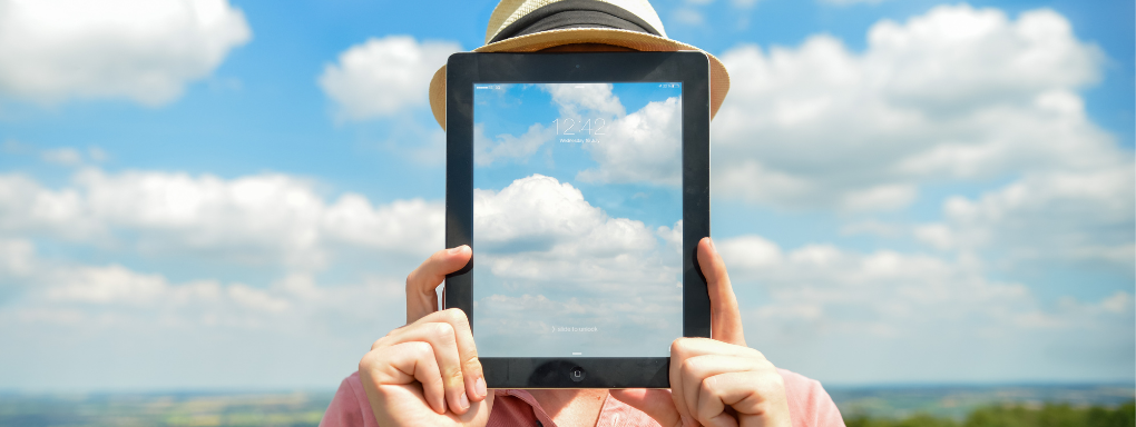 Man with Ipad covering his face which a screensaver which matches the sky and clouds in the background giving the illusion of transparency.