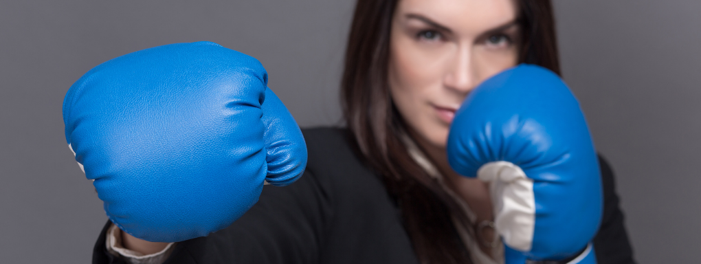 Female business woman with blue boxing gloves punching towards the camera
