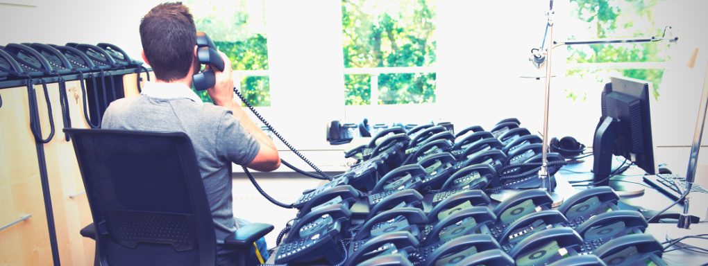 Man with hundreds of old corporate telephones sat on his desk