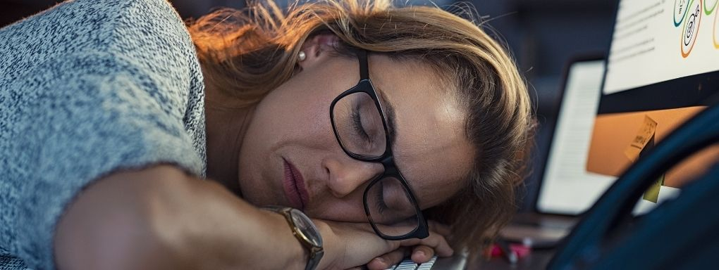 Woman asleep at office desk still wearing her glasses
