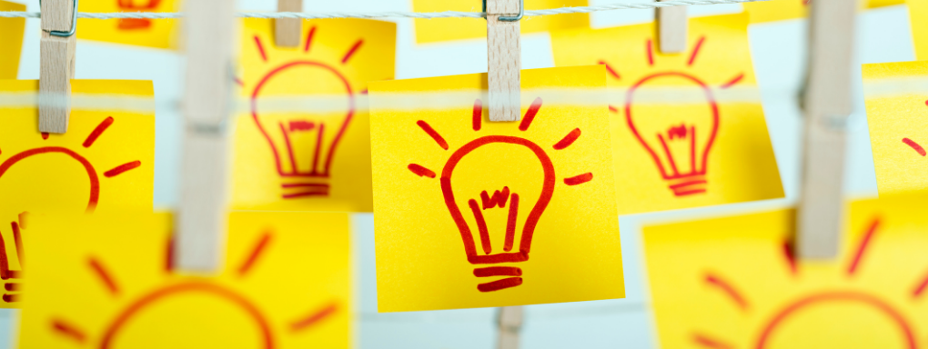 Yellow post-it notes with red lightbulb drawings pegged to a washing line