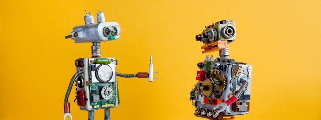 Two robots, one passing a screwbit to another one on a yellow backdrop.