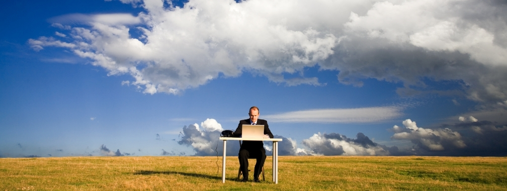 Man sitting at a desk in an empty field with blue skies